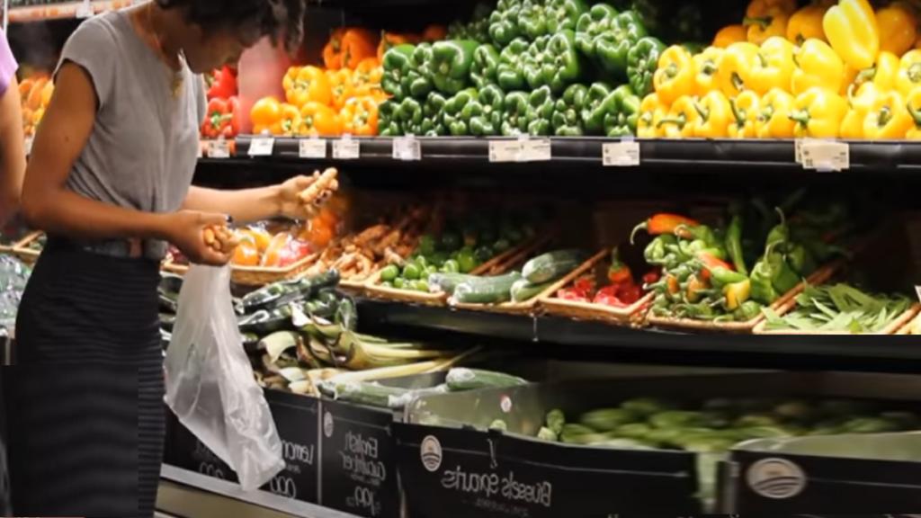 человек выбирает овощи и фрукты в магазине